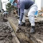 """隊員たちは、側溝の汚泥をスコップで懸命に取り除いた(2015年9月21日、茨城県常総市の玉小学校で)"""""""
