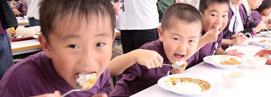 昼食のカレーを食べる子供たち