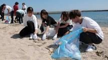 学生たちは海岸のごみを丁寧に拾い集めた(15日、神戸市の須磨海岸で)
