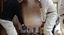 水を含んで重たくなったタンスを運び出す宮崎教区隊の隊員(9月4日)