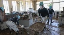 職員室内に流入した土砂を、手作業で搬出する隊員たち(7月22日、球磨村の渡小学校で)